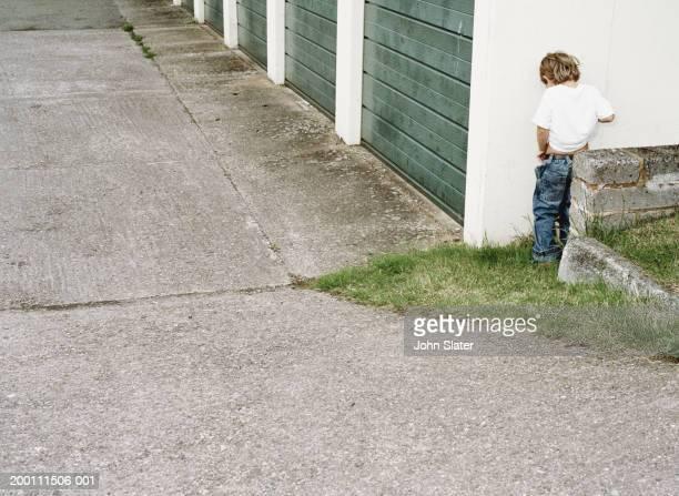 Boy (4-6) urinating against garage wall, rear view
