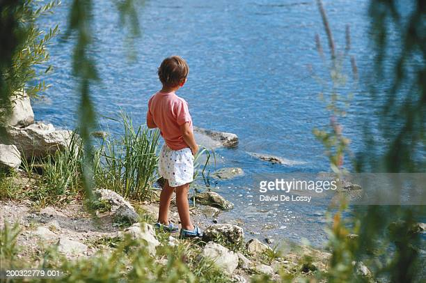 boy (4-5) urinating by river, rear view - kids peeing stock pictures, royalty-free photos & images