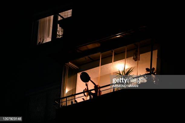 A boy uses a pan and a spoon to make noise from his balcony in Pristina on March 20 2020 as measures are in place to attempt to prevent the spread of...