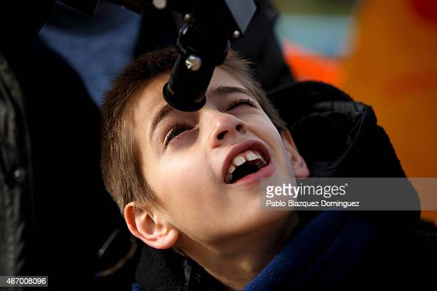 A boy uses a telescope to look into the sky during a partial solar eclipse outside the Planetario on March 20 2015 in Madrid Spain In Madrid the moon...