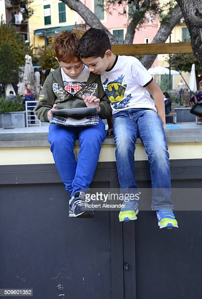A boy uses his Apple tablet computer as his friend looks on in the seaside town of Monterosso on Italy's northwest coast one of five villages which...