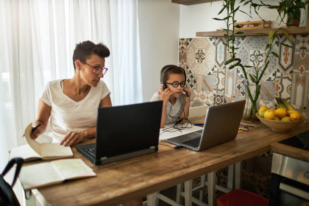 boy uses laptop while his mother working from home - parents and children  stock pictures, royalty-free photos & images