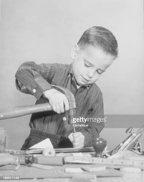 Boy using a hammer and other tools while building something Philadelphia PA 1958