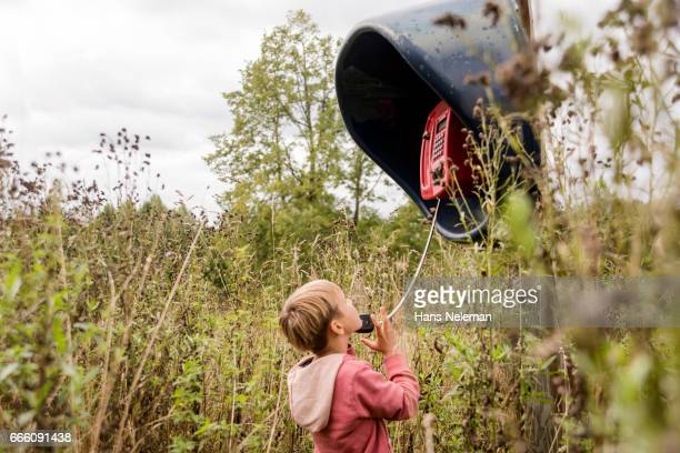 Boy using a pay phone in the field