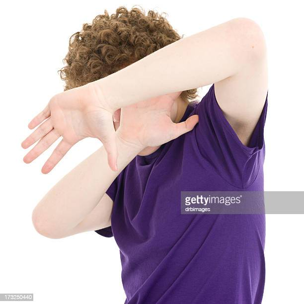 Boy Using Arms To Shield Himself From Camera