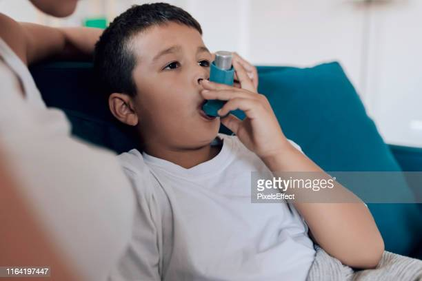 boy using asthma inhaler - cystic fibrosis stock photos and pictures