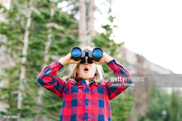 Boy (6-7) using binoculars in forest