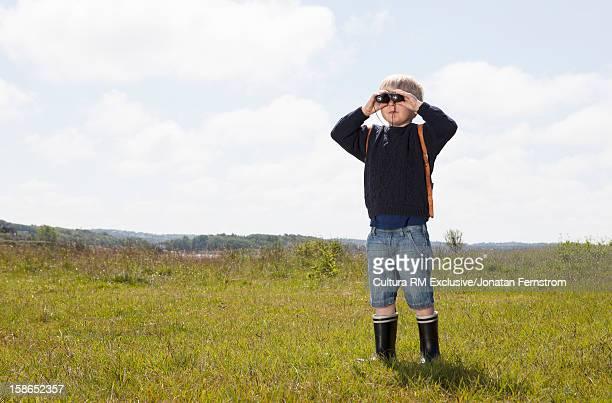 Boy using binoculars in grassy field