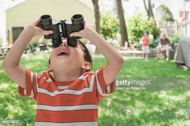 Boy using binoculars outdoors