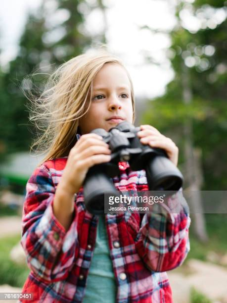 Boy (6-7) using binoculars