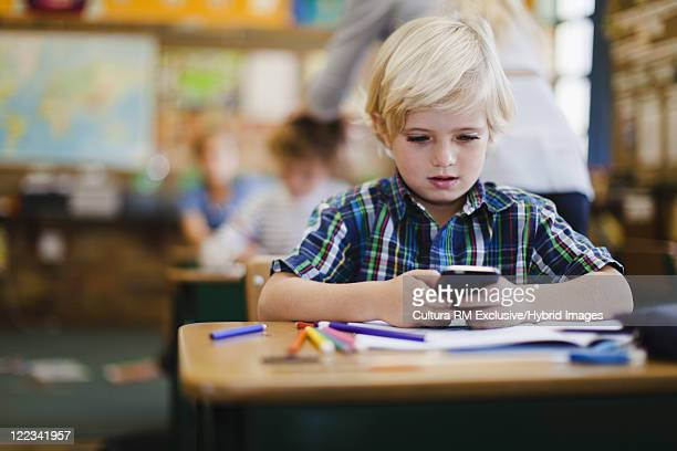 Boy using calculator in class