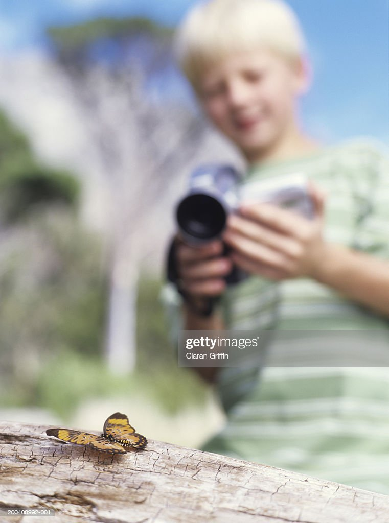 Boy (8-10) using camcorder to film butterfly, close up : Stock Photo