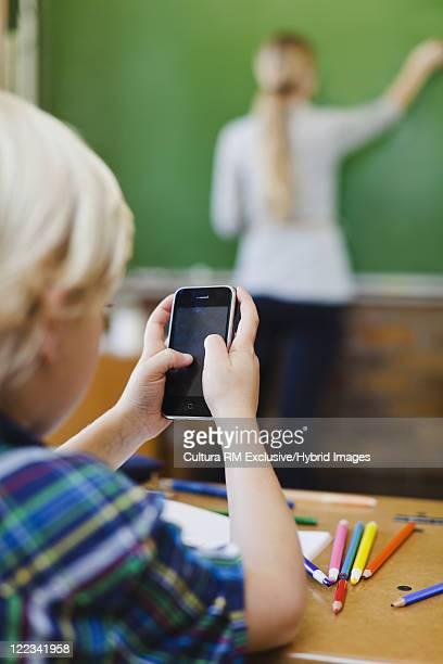 Boy using cell phone in class