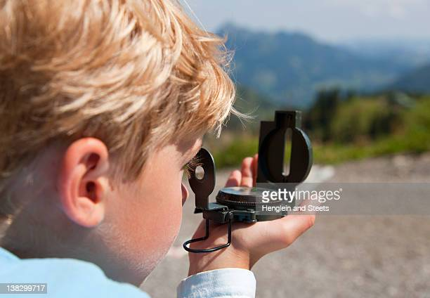 boy using compass outdoors - compass stock photos and pictures