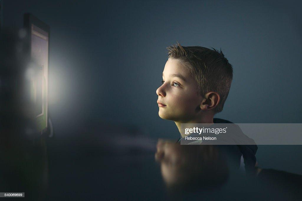 boy using computer at night : Stock Photo