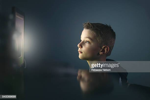 boy using computer at night - rebecca nelson stock pictures, royalty-free photos & images