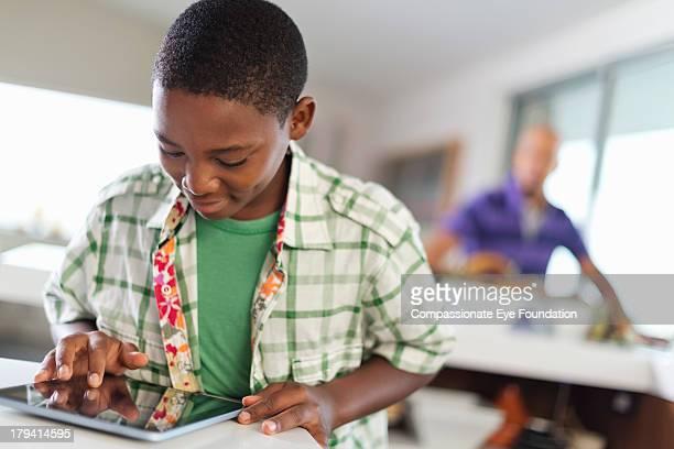 Boy (11-12) using digital tablet in kitchen