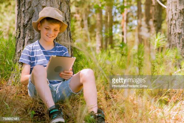 boy using digital tablet in woods - free download photo stock photos and pictures