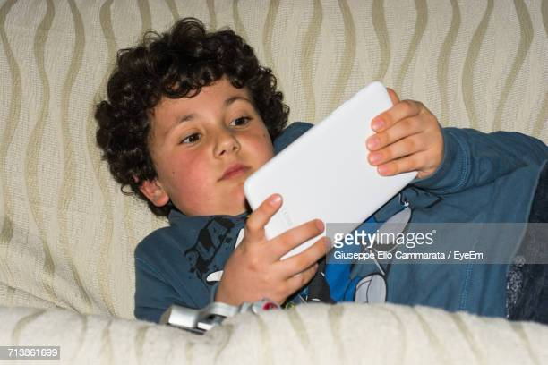 boy using digital tablet on sofa at home - cammarata stock photos and pictures