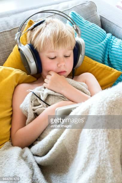 boy using digital tablet on sofa - bank zitmeubels stockfoto's en -beelden