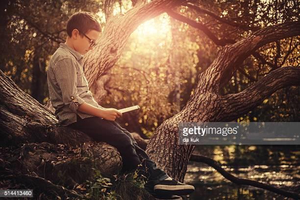 Junge mit digitalen tablet Sitzen im park bei Sonnenuntergang