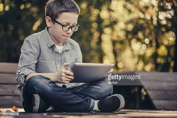 Boy using digital tablet sitting in the park