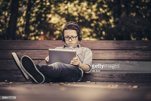 Junge mit digitalen tablet Sitzen im park