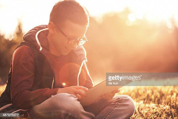 Boy using digital tablet sitting on a grass at sunset