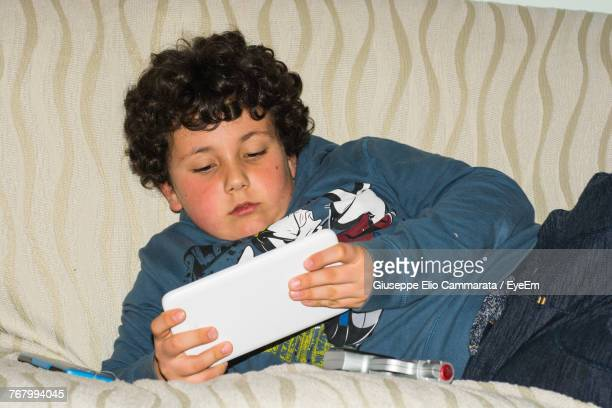 boy using digital tablet while reclining on sofa at home - cammarata stock photos and pictures