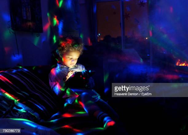Boy Using Digital Tablet While Sitting At Illuminated Bedroom