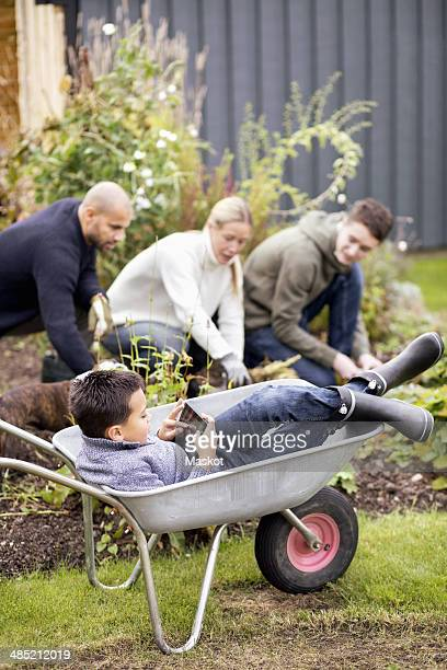 Boy using digital tablet while sitting in wheel barrow with family gardening in background