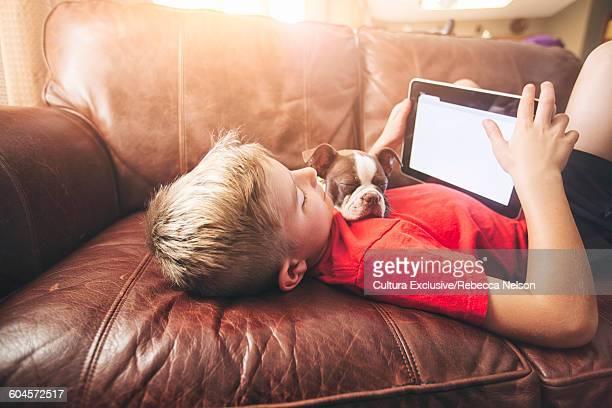 Boy using digital tablet whilst boston terrier pup asleep on sofa