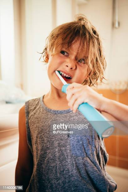 boy using electric toothbrush to brush teeth, pulling face - electric toothbrush stock pictures, royalty-free photos & images