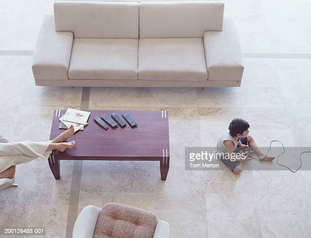 Boy (4-6) using games console on floor, woman on sofa, elevated view