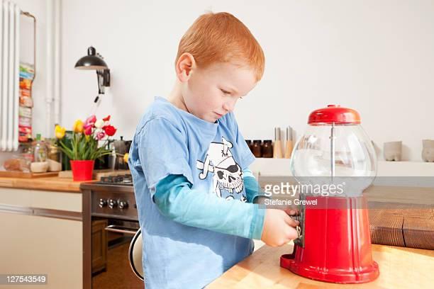 Boy using gum ball machine in kitchen