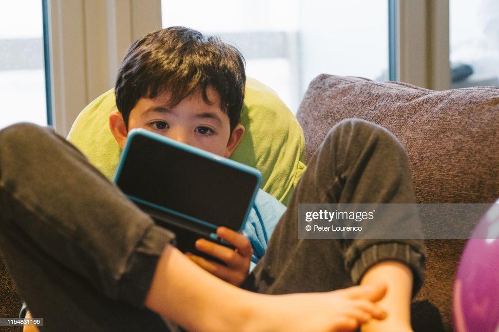 Boy using handheld computer game : Stock Photo