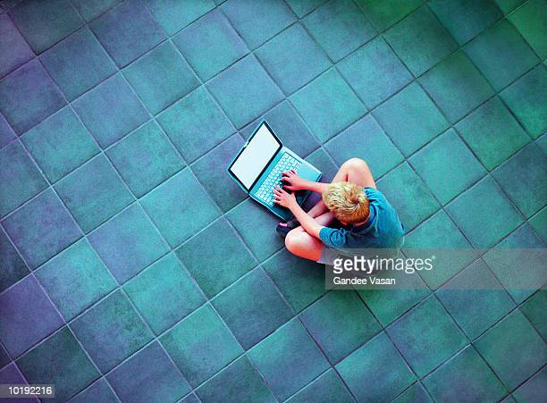 Boy (10-12) using laptop computer on floor, elevated view