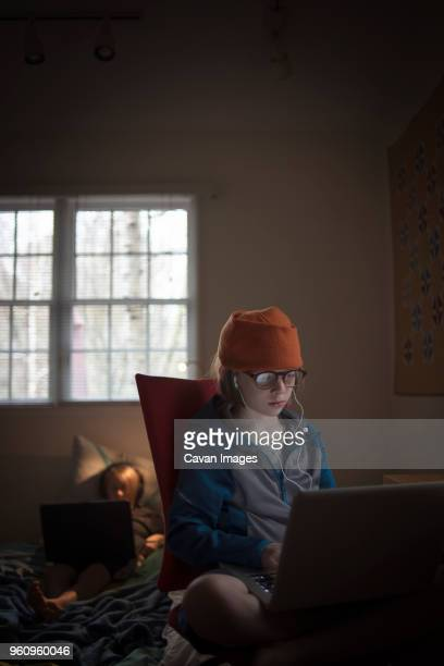 Boy using laptop computer while sitting on chair at home