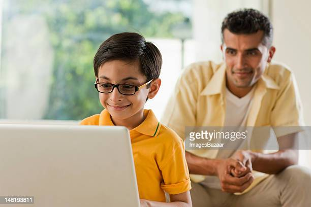 Boy (6-7) using laptop, father in background