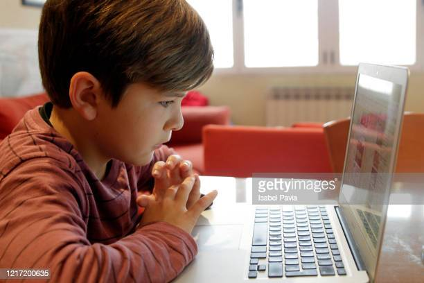 boy using laptop for homework or homeschooling - homeschool stock pictures, royalty-free photos & images