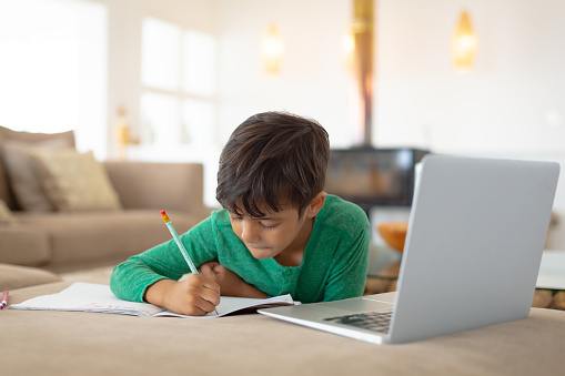 Boy using laptop while drawing a sketch on book at home 1159559400