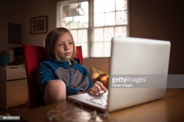 Boy using laptop while sitting at table