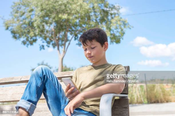Boy Using Mobile Phone While Sitting On Bench Against Sky