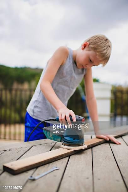 menino usando lixadeira orbitando uma prancha de madeira - orbiting - fotografias e filmes do acervo