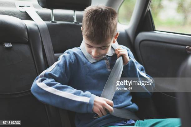 Boy using safety seat belt in a car