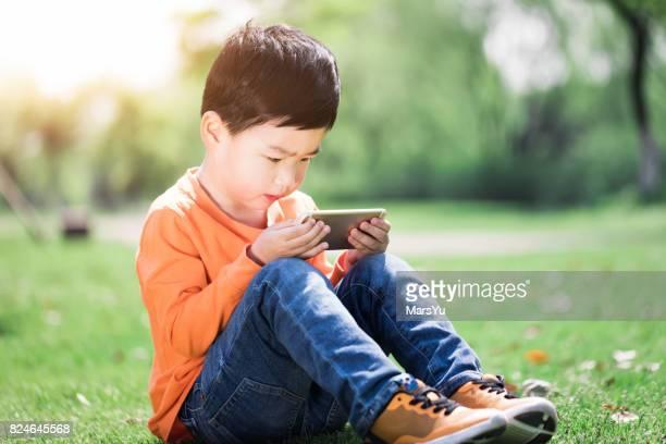 Boy Using Smart Phone at park