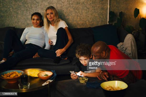 boy using smart phone by father while mother and daughter sitting on sofa during sporting event - sweden stock pictures, royalty-free photos & images