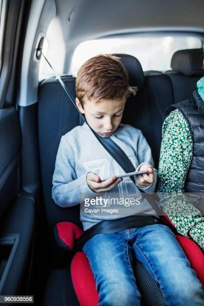 Boy using smart phone in car