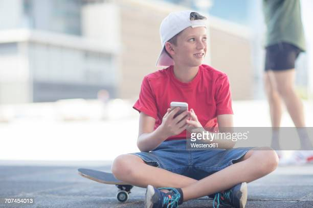 Boy using smart phone, sitting on skateboard