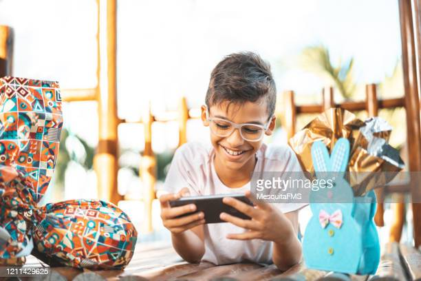 boy using smartphone and celebrating easter - happy easter text stock pictures, royalty-free photos & images